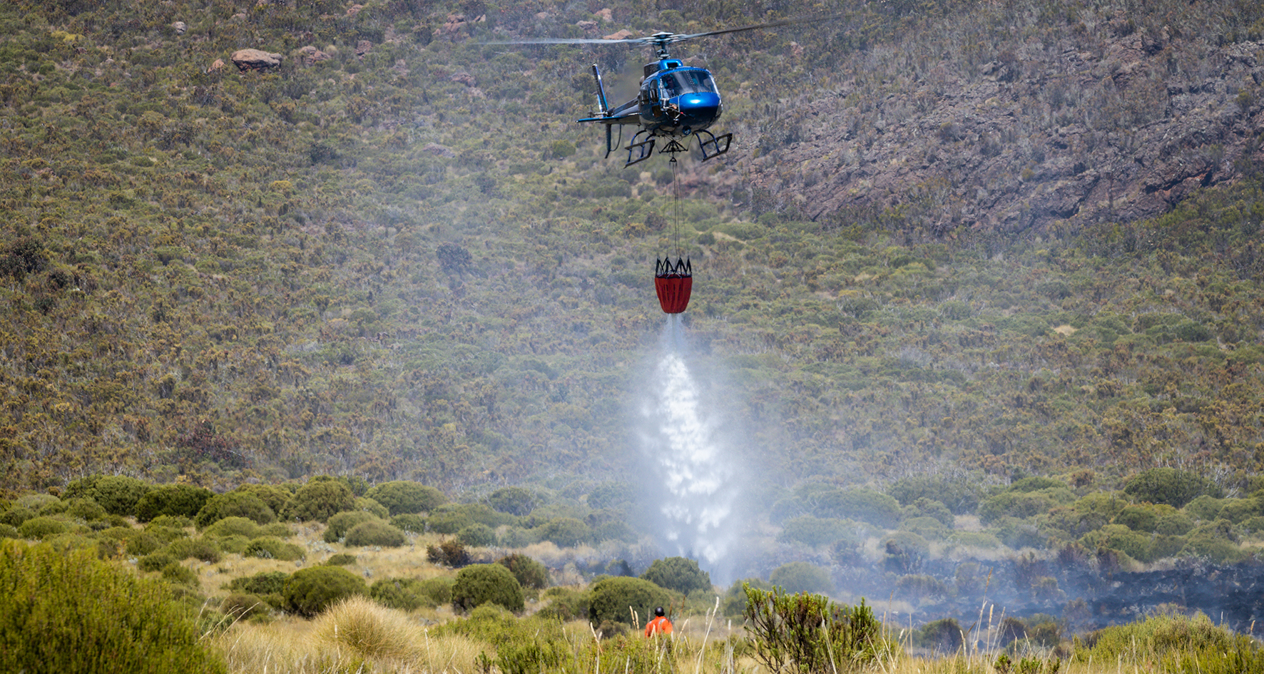 helicopter dropping water on fires, Mount Kenya